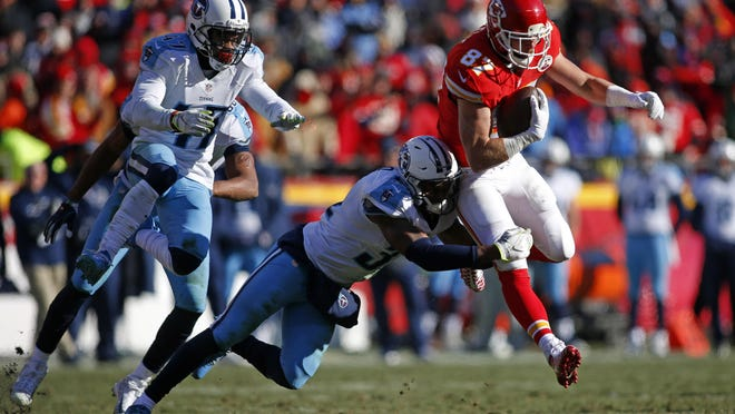 Chiefs tight end Travis Kelce (87) is tackled by Titans safety Kevin Byard (31) during the first half Sunday.