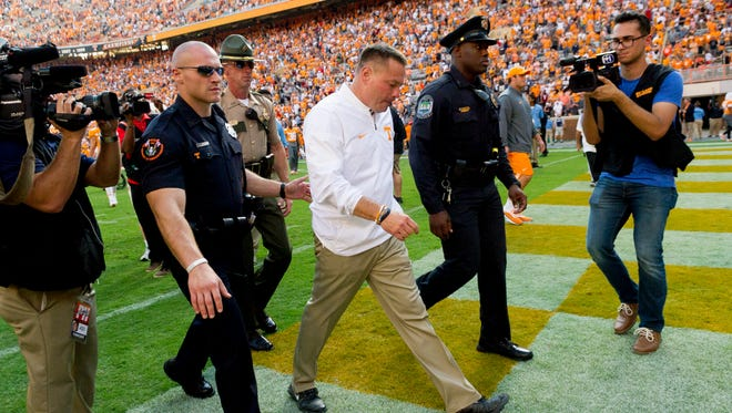 Tennessee coach Butch Jones is escorted from the field after the game against South Carolina on Oct. 14, 2017, at Neyland Stadium.
