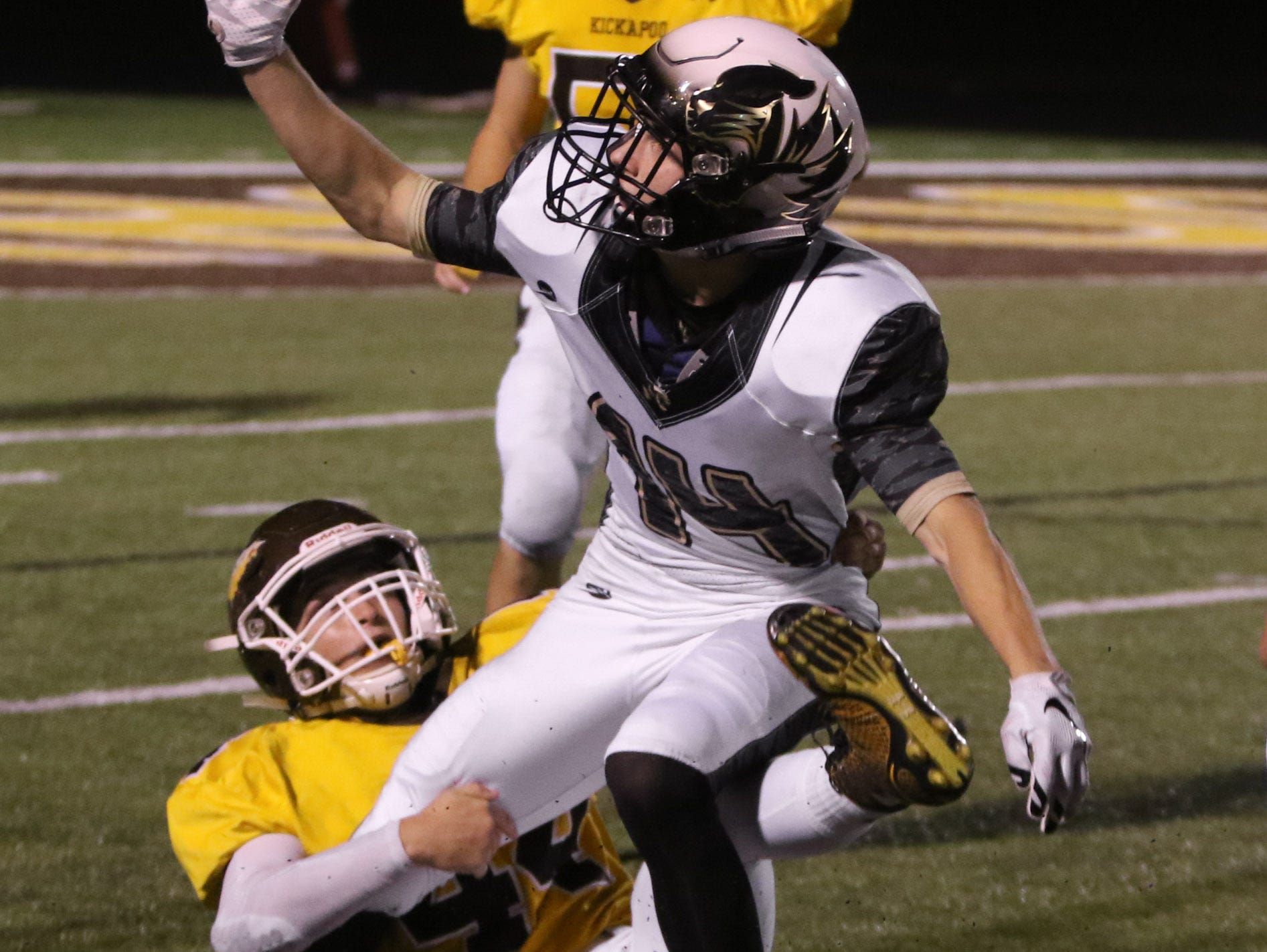 Kickapoo High School linebacker Tre Woodring forces a turnover in the second half against Lee's Summit High School Friday, October 23, 2015. Jason Connel / For the News-Leader