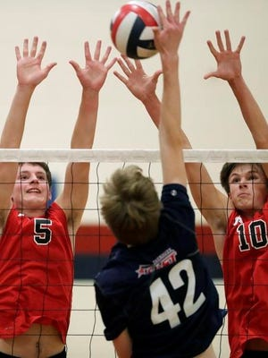 Appleton East's Eli Jenn (42) hits a shot against Kimberly's Kevin Liind (5) and Ben Rambo (10) during a Fox Valley Association boys volleyball quadrangular Tuesday at Appleton East.