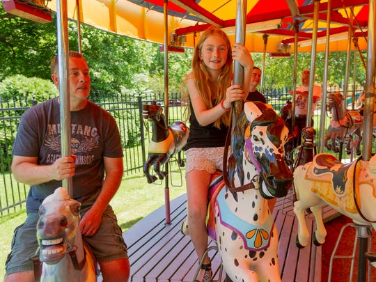 Mike McCall and his nine-year-old Anna, of Spencer ride the carousel in Stewart Park Saturday afternoon. Rides were free on Saturday afternoon as the Friends of Stewart Park held a dedication for the new fence around the carousel.
