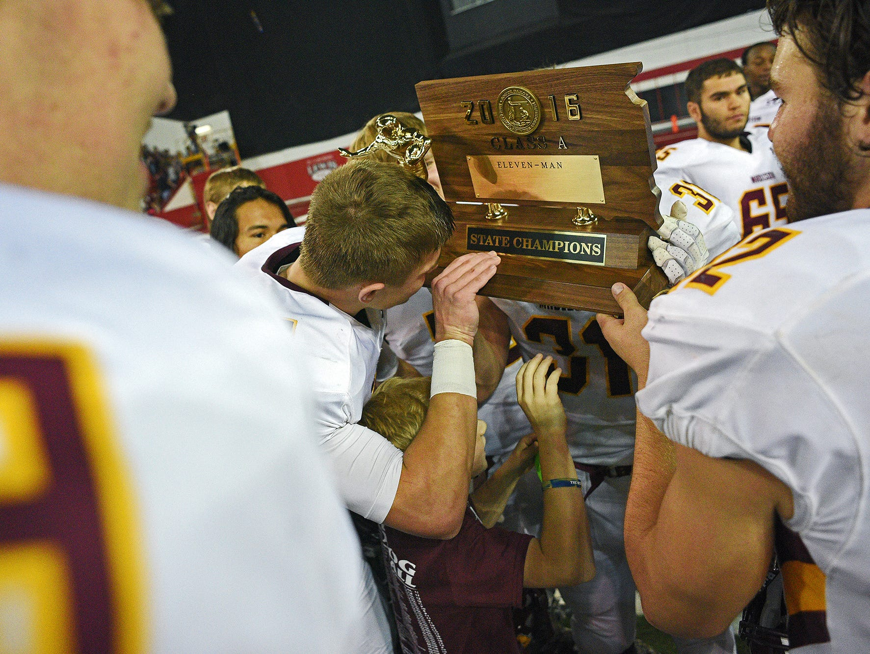 Madison's Jaxon Janke (6) kisses their trophy while celebrating their 39-0 win over Tea Area with their fans and families after the 2016 South Dakota State Class 11A Football Championship game Saturday, Nov. 12, 2016, at the DakotaDome on the University of South Dakota campus in Vermillion, S.D.