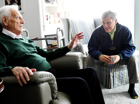 Former MSU basketball coach and radio broadcaster Gus Ganakas, left, reflects on his time at the university with his son Gary, right, on March 8 at his home in East Lansing. Gary played for his father at the school.