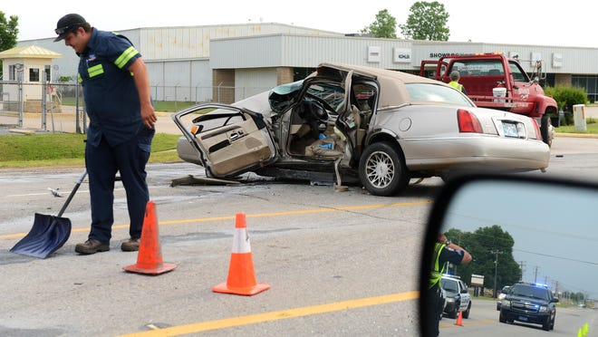 Workers clean up debrise as police work the scene of a fatal wreck on Thursday, May 11, 2017, on Zero Street in Fort Smith.