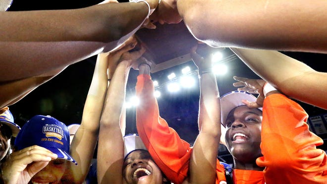 Blackman's Taylor Freeman, Crystal Dangerfield and MeMe Jackson hold up the TSSAA Class AAA girls basketball state championship trophy.