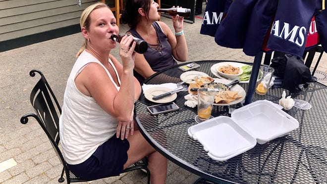Caryn Thielker, left, and Dawn Velazquez top off their lunch at Raynham's Stoneforge restaurant in Raynham with a beer.