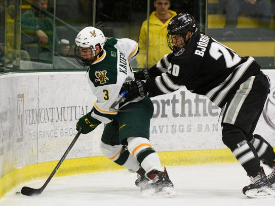 Vermont forward Max Kaufman (3) plays the puck while