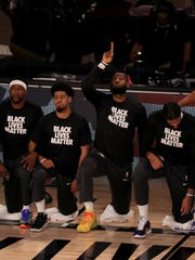 Los Angeles Lakers' LeBron James wears a Black Lives Matter shirt as he points up and kneels with teammates during the national anthem prior to an NBA basketball game against the Los Angeles Clippers, Thursday, July 30, 2020, in Lake Buena Vista, Fla. (Mike Ehrmann/Getty Images via AP, Pool)