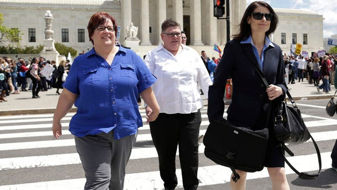 April DeBoer, left, crosses First Street in front of the U.S. Supreme Court in Washington D.C. Tuesday Apr. 28, 2015 with their attorney Dana Nessel.