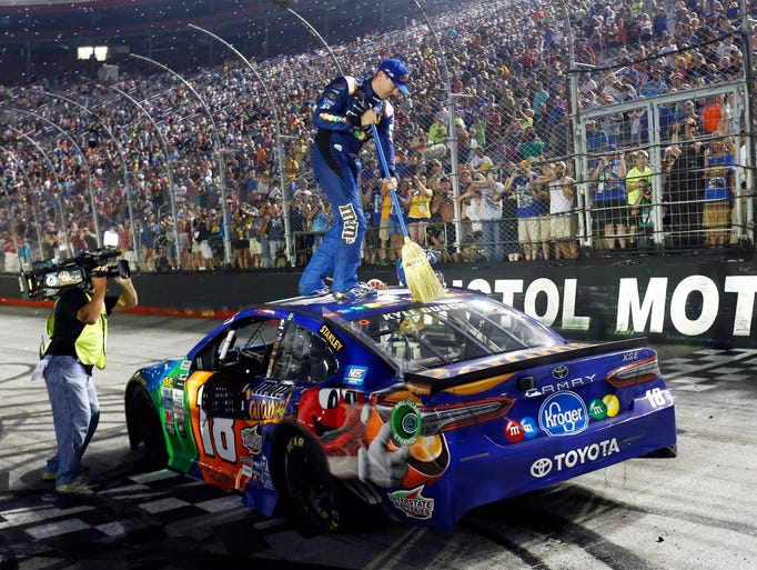 Kyle Busch sweeps the top of his car after winning