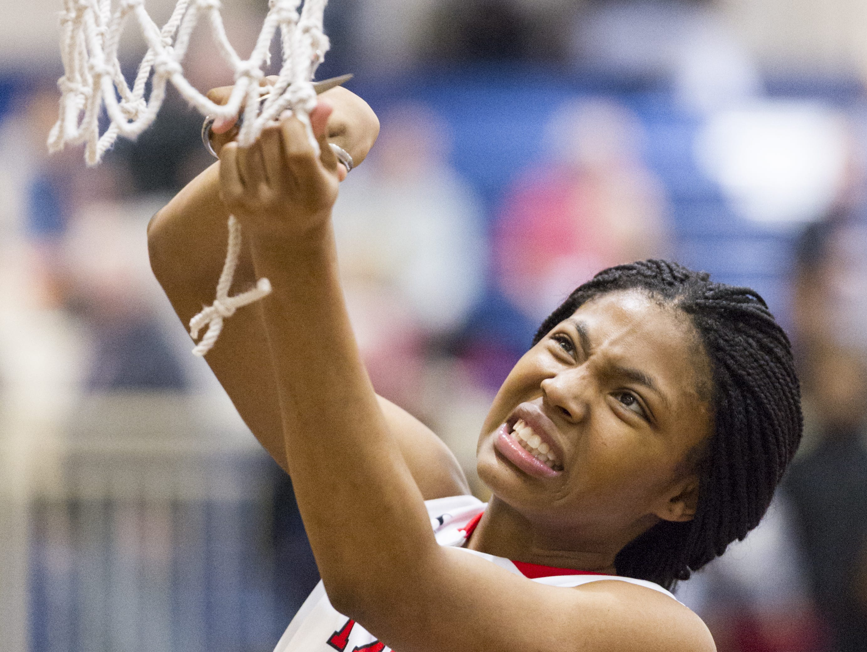 Pike High School junior Angel Baker (15) grimaces as she struggles to cut down a piece of the game net after winning the IHSAA 4A Girls' Basketball Tournament Regional championship game, Saturday, Feb. 11, 2017, at Decatur Central High School. Pike won in overtime, 61-59.