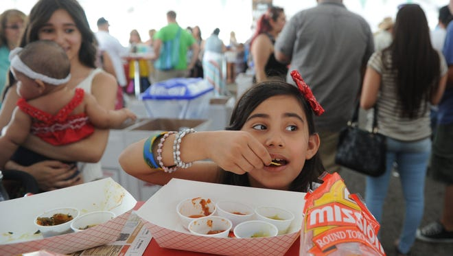 Divinity De La Rosa, 8, tastes the different types of salsa at the Salsa Festival in 2015.