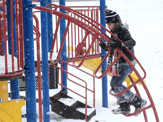 Lachlann Arlund, 10, climbs on a jungle gym in the