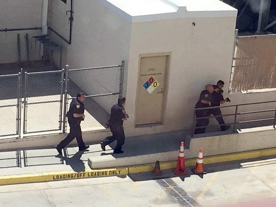 Law enforcement agents walk along the exterior of the