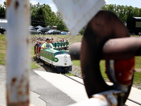 "Conductor Art Sullivan steers a 15"" gauge train at"