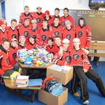 Churchill hockey players pose with the school supplies they collected for DPS students.