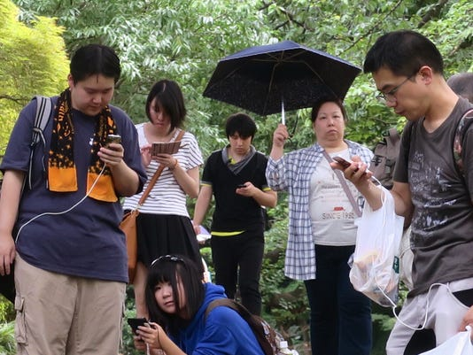 """In this Thursday, June 28, 2016 photo, Pokemon hunters crowd under a green canopy with their mobile phones as they play """"Pokemon Go"""" in the Shinjuku Gyoen National Garden in Tokyo. Japanese Olympic gymnast Kohei Uchimura was stunned to receive a 500,000 yen ($4,900) mobile phone bill after playing the popular augmented-reality game, Kyodo news agency reported Tuesday, Aug. 2. Thankfully for him, his Japanese carrier service agreed to reduce his bill to a 3,000 yen ($30) daily all-you-can-use contract, Kyodo said. (AP Photo/Hiroshi Otabe)"""