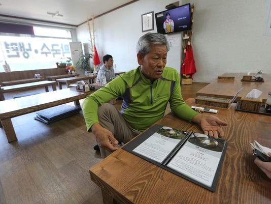 "In this Oct. 30, 2017, photo, owner Lee Do-sung speaks during an interview at his restaurant in Gangneung, South Korea. Worries over costs have cast a shadow over the 2018 Pyeongchang Winter Olympic Games among residents long frustrated with what they say were decades of neglect in a region that doesn't have much going on other than domestic tourism and fisheries. ""What good will a nicely managed global event really do for residents when we are struggling so much to make ends meet?"" said Lee. ""What will the games even leave? Maybe only debt."" (AP Photo/Ahn Young-joon)"