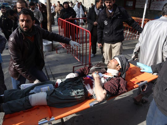 People help carry an injured man to the hospital following a suicide attack in Kabul, Afghanistan, Saturday Jan. 27, 2018. The Public Health Ministry says over a dozen were killed, and over 100 wounded in a suicide car bombing in downtown Kabul. (AP Photo/ Rahmat Gul)