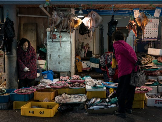 A woman shops for fish at the traditional market in Gangneung, South Korea, Tuesday, Feb. 13, 2018. While the Winter Olympics are going on in the mountains, some serious haggling is underway on the coast. One part of the Pyeongchang area that hasn't been Westernized and beautified for the Winter Olympics is the traditional market in Gangneung, several blocks of street stalls operated for the most part by old women who are decidedly no-nonsense about selling their wares - from naturally dried octopus legs to goopy globs of seaweed freshly harvested from the local waters.  (AP Photo/Felipe Dana)