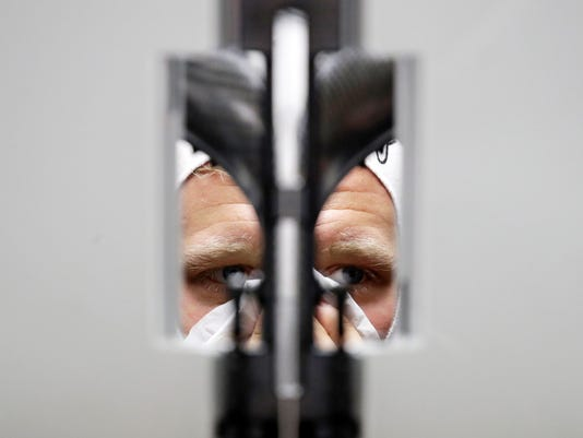 Haas driver Kevin Magnussen of Denmark wipes his face as he prepares for the first practice session for the Chinese Formula One Grand Prix at the Shanghai International Circuit in Shanghai, Friday, April 13, 2018. (AP Photo/Andy Wong)