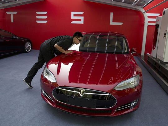 A worker cleans a Tesla Model S sedan before an event to deliver the first set of cars to customers in Beijing. U.S. auto companies such as General Motors, Tesla and Ford faltered this year in Consumer Reports' reliability rankings as readers reported more mechanical trouble and fewer problems with infotainment systems.
