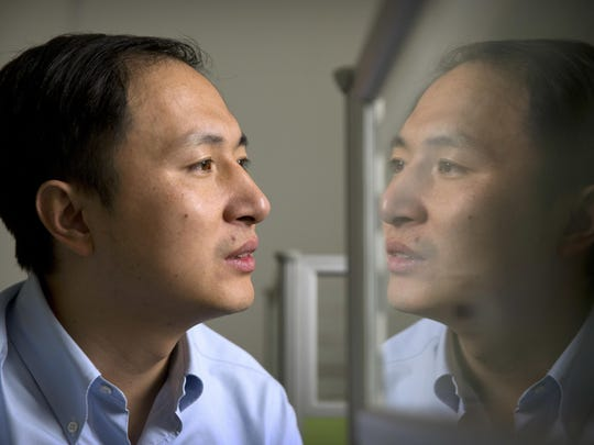 He Jiankui is reflected in a glass panel as he works