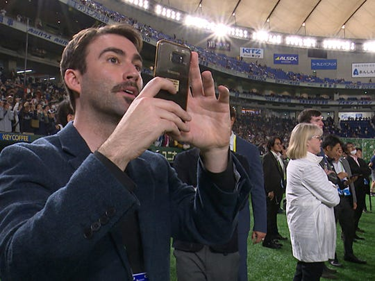 """In this Thursday, March 21, 2019, image from video, Joey Mellows from Portsmouth, England, watches the Seattle Mariners' batting practice before Game 2 of the Major League Baseball opening series between the Mariners and the Oakland Athletics at Tokyo Dome in Tokyo. Mellows, better known by his Twitter feed """"Baseball Brit,"""" has quit his job to watch an entire season of Major League Baseball games. Some may see it as a frivolous pursuit but others are impressed by his free spirit. (SNTV via AP)"""