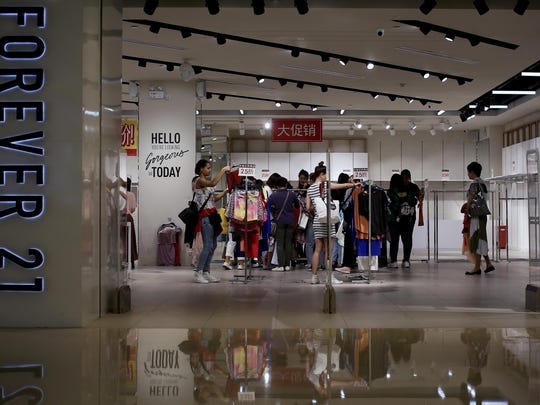 """Women select clothing at an American fast fashion retailer """"Forever 21"""" which is offering clearance discounts at a shopping mall after it pulled out from China's market, in Beijing, Tuesday, May 7, 2019. China confirmed Tuesday its economy czar will go to Washington for trade talks despite fears he might cancel after President Donald Trump threatened to escalate a tariff war over Beijing's technology ambitions. (AP Photo/Andy Wong)"""
