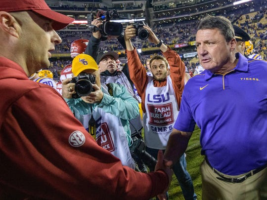 LSU coach Ed Orgeron, right, greets Arkansas coach Barry Lunney Jr. after LSU's 56-20 victory in an NCAA college football game in Baton Rouge, La., Saturday, Nov. 23, 2019. (AP Photo/Matthew Hinton)