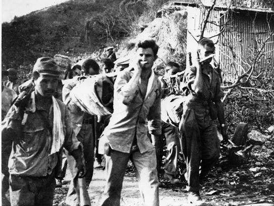 American prisoners of war carry their wounded and sick