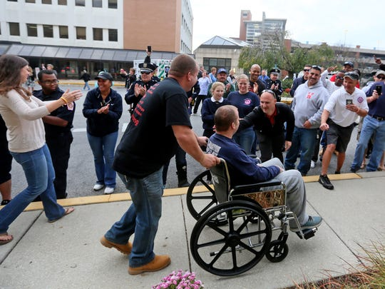 Firefighter Brad Speakman, a city firefighter injured in a deadly Canby Park blaze in September, was greeted by family, friends and fellow emergency workers as he checked out of a Pennsylvania hospital Thursday.