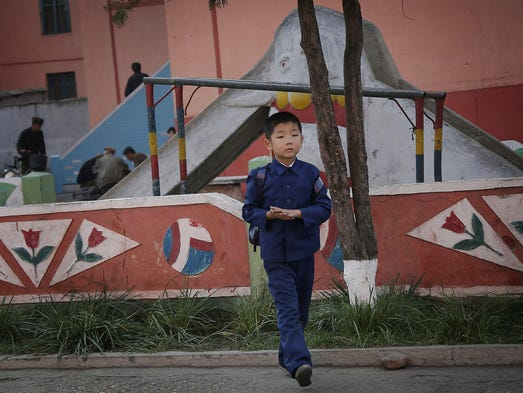 A North Korean boy in his school uniform walks past