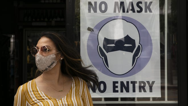 A woman walks out of a liquor store past a sign requesting its customers to wear a mask in Santa Monica, Calif. Scientists are warning that a new bout with the coronavirus this fall could claim more lives.