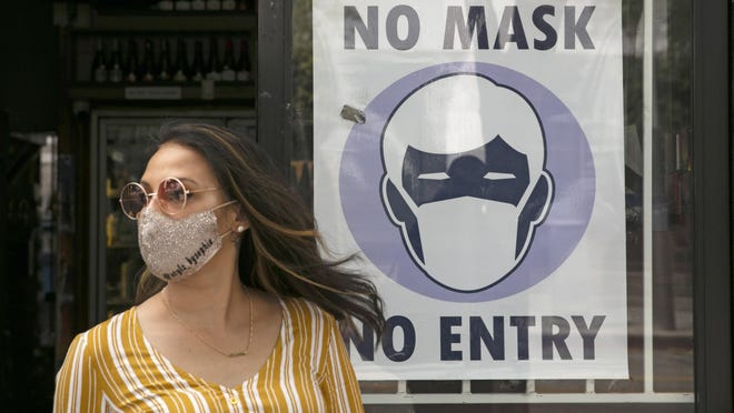 FILE - A woman walks out of a liquor store past a sign requesting its customers to wear a mask Tuesday, June 23, 2020, in Santa Monica, Calif. According to a new poll, Americans overwhelmingly are in favor of requiring people to wear masks around other people outside their homes, reflecting fresh alarm over spiking infection rates. The poll also shows increasing disapproval of the federal government's response to the pandemic. California is among the states seeing the greatest surge in cases now.