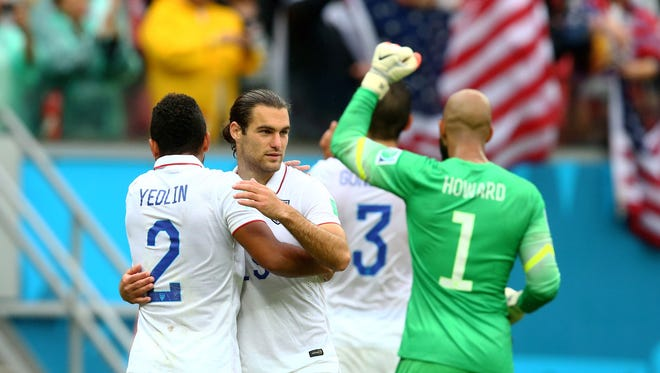 USA defender DeAndre Yedlin (2) celebrates with midfielder Graham Zusi (center) and goalkeeper Tim Howard following the game against Germany during the 2014 World Cup at Arena Pernambuco on June 26, 2014.