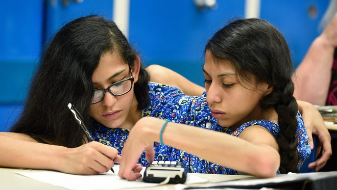 "Carmen and Lupita Andrade work together in math class on Sept. 13, 2016 at Nonnewaug High School in Woodbury, Ct. In a class last fall, the twins' English teacher was describing an assignment to the class, and noted that if they wanted to they could tackle parts of an assignment separately. ""You know we can't be separated,"" Carmen quipped."
