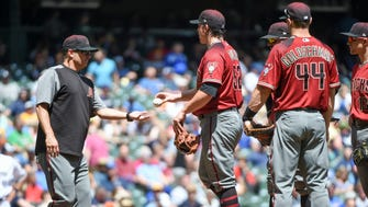 Arizona Diamondbacks pitcher Zack Godley (52) hands the ball to manager Torey Lovullo during a pitching change in the fourth inning during the game against the Milwaukee Brewers at Miller Park.