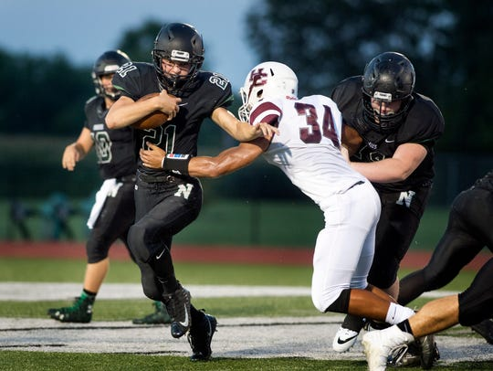 North High School's Dylan McKinney, left, runs past