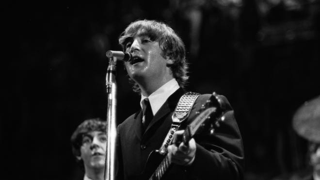 In this 1964 photo made by Walt Burton and provided by Christopher Hoeting, John Lennon, front, and Paul McCartney, of the Beatles, perform during a concert in Cincinnati.
