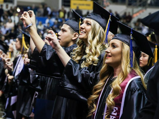 Graduates participate in the school song at the conclusion of the Angelo State University commencement ceremony Saturday, Dec. 16, 2017, at Junell Center.