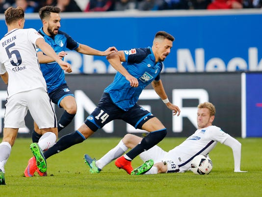 Hoffenheim's Sandro Wagner, center, and Hertha Berlin's Fabian Lustenberger challenge for the ball during a German first division Bundesliga soccer match between TSG 1899 Hoffenheim and Hertha BSC Berlin in Sinsheim, Germany, Sunday, Oct. 30, 2016. (AP Photo/Michael Probst)