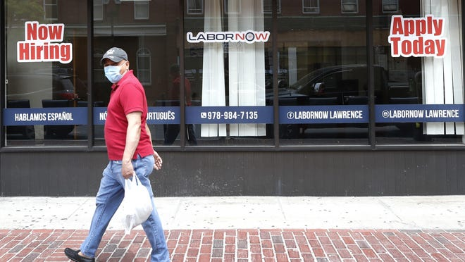 A man walks by a career center storefront, Friday, June 5, 2020, in Lawrence, Mass. The U.S. unemployment rate fell unexpectedly in May to 13.3%, which is still on par with what the nation witnessed during the Great Depression.