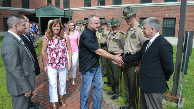 Retiring Vermont State Police Director Col. Tom L'Esperance, accompanied by his family, makes his final departure form headquarters in Waterbury on Friday.