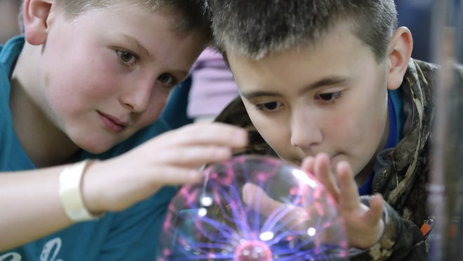 Jackson Elementary School students Cody Nowack and Maximus Schreiber check out the plasma ball station at Mind Trekkers, a traveling science awareness program that stopped at Northeast Wisconsin Technical College this week
