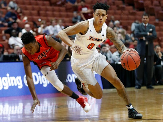 Cal State Fullerton's Kyle Allman, right, drives past Cal State Northridge's Micheal Warren during the second half of an NCAA college basketball game at the Big West conference men's tournament on Thursday, March 9, 2017, in Anaheim, Calif. Cal State Fullerton won 81-68. (AP Photo/Jae C. Hong)
