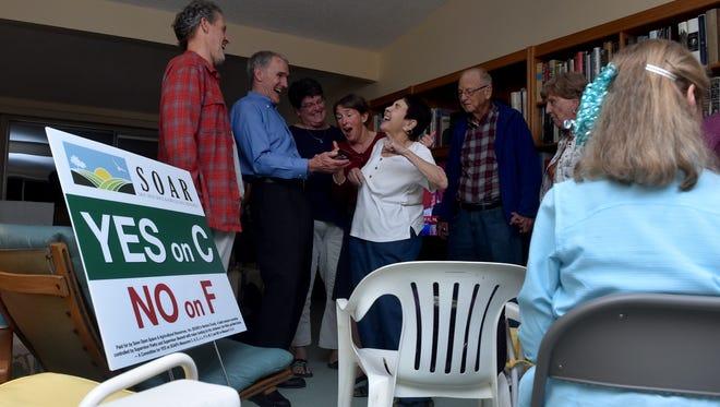 Kris Young (left to right), Steve Bennett, Karen Schmidt, Leslie Ogden, Debbie Diamond, Tom Jones and Rose Jones react as votes for Measure C climb during an election night party in Ventura on Tuesday.