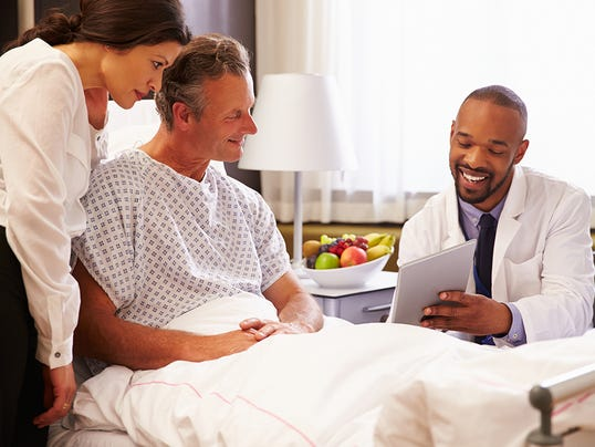 Doctor Talking To Male Patient And Wife In Hospital Bed
