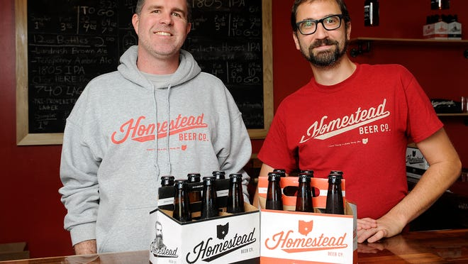 Homestead Beer Co. co-founders and owners Kevin Atkinson and Adam Rhodes with the two beers now offered in six packs of 12-oz. bottles. The two beers are the 1805 IPA and Tenpenny Amber Ale brewed at their Heath location.