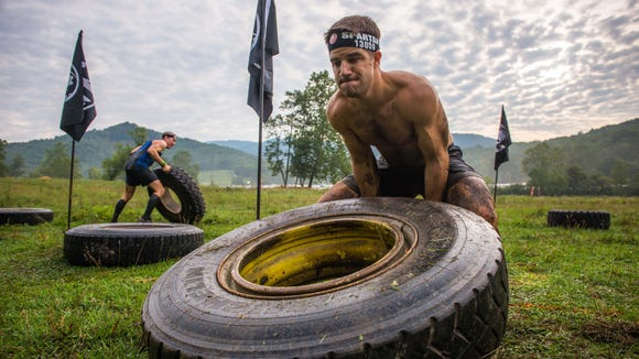 Matthew Zangle tests his might on the tire flip obstacle during the Spartan Race last year in Black Mountain. The second annual race through mud and obstacle pits is Aug. 6 at Grove Stone Quarry.
